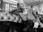 Mujer riendo sentada en un sofá con su perro